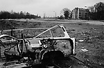 A wrecked shell of an East German Trabant motor car near a section of the course of the former Berlin Wall, Bornholmer Strasse, Berlin. The Berlin Wall was a barrier constructed by the German Democratic Republic (GDR, East Germany) starting on 13 August 1961, that completely cut off West Berlin from surrounding East Germany and from East Berlin. The Wall was opened on 9. November 1989 allowing free movement of people from east to west.