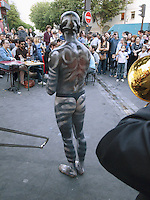 France. Department Ile-de-France. Paris. A naked man dances in front of a cafe in the Belleville area (10th district). He has fully painted his body and looks like a zebra. 19.05.2011 © 2011 Didier Ruef