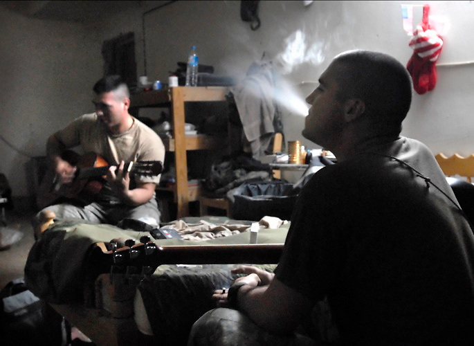"Spc. Josh Somma (left) and Spc. Brian Ahern, of Headquarters and Headquarters Troop, 1-32 CAV, play original songs like,""I Eat IEDs for Breakfast"" in their living quarters in Muqdadiyah, Iraq."