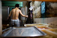 Zhu Zhi Qiang, 19, prepares food for an order at Gang Shan Zha Zha, a popular streetside hotpot restaurant on Tiyu Road in central Yuzhong distrist, Chongqing, China. Zhu Zhi Qiang, having worked at the restaurant for four years, said &quot;I want to open a shop like this one day.&quot;<br /> <br /> The restaurant sits on the site of a former neighborhood garbage collection point and &quot;zha zha&quot; is local slang for &quot;garbage.&quot; The restaurant has been open for 5 years and recently opened a second location elsewhere in Chongqing. A manager of the restaurant said that they server 60-70 tables every night, with many tables' bills coming to over 1000RMB. The restaurant often has a long wait. The site is well-reviewed on online restaurant sites similar to Yelp and is known for having good flavor, serving fresh food, and being clean.