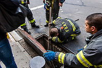New York, NY 9 November 2014 - Fire fighters using tools to fetch lost keys that fell down a sewer.