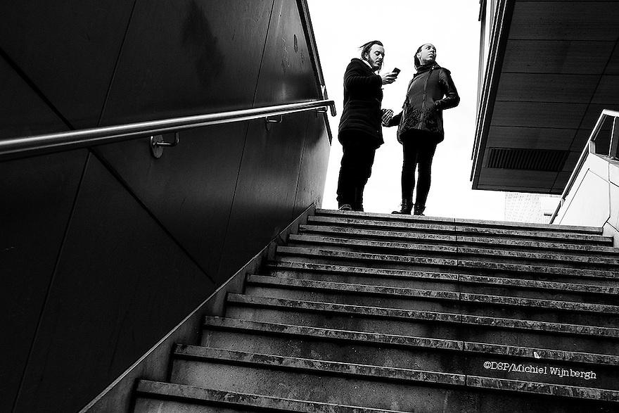 Nederland, Amsterdam, 31 jan 2015<br /> Jong stel overlegt en raadpleegt smart phone nabij ns station Amsterdam Zuid.<br /> <br /> Foto: (c) Michiel Wijnbergh