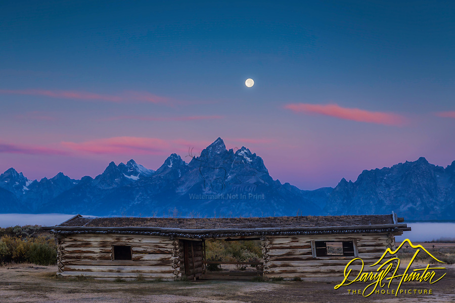 Setting moon at sunset over the Grand Tetons and the Cunningham Cabin in Grand Teton National Park.  The Cunningham Cabin was one of the original homsteader cabins of Jackson Hole Wyoming