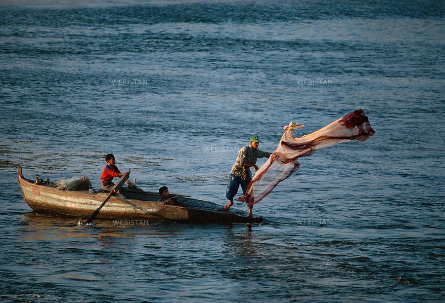 Egypt. 1996. A fisherman throws his net on the Nile waters. A young boy drives the rowing boat..Egypte. 1996. Un pecheur lance son filet sur les eaux du Nil. A la rame, un jeune garcon assure la manoeuvre de la barque..