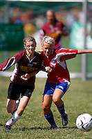 Two girls from Norwegian teams battle for the ball. Norway Cup is the worlds largest football tournament, in 2008 bringing together 30.000 children from all over the world, aged 10 to 19. They make up 1386 teams playing a total of 4400 matches during the week they play. The tournament is played on a big grass field just outside the center of Oslo, Norway.