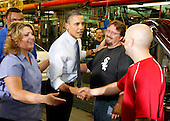 United States President Barack Obama greets an assembly line worker Jeffrey Crook as he tours through the Chicago Ford Motor Company Plant, Thursday,  August 5, 2010. .Credit: Jeff Haynes - Pool via CNP