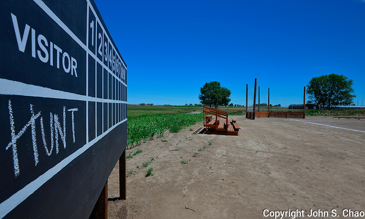 """Reconstructed Hunt Camp's Baseball scoreboard and field (with rows of planted corn for """"Field of Dreams"""" reference), with barracks in backdrop. At Minidoka National Historic Site, in Jerome, Idaho, where Japanese-American citizens were forcibly incarcerated during World War II."""