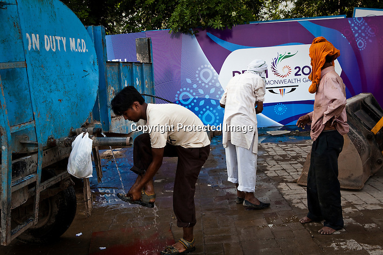 Local residents use government water supply trucks to wash outside the Commonwealth Games hoarding that hides their slums in New Delhi, India.