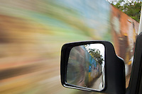 Images of the great wall of Tortola murals painted by local artist's sceen in the side view mirror