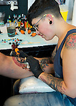 Garden City, New York, USA. 14th September 2014. Tattoo artist DEBORA CHERRYS, from Spain, tattoos the leg of ANTHONY MEISTER, of Seaford, at the United Ink Flight 914 tattoo convention at the Cradle of Aviation museum of Long Island.