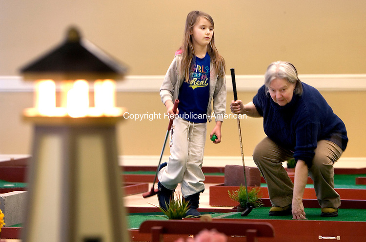 WOODBURY CT. 15 February 2014-021514SV03-From left, Shelby Snowden, 7, of Woodbury and her grandmother Millie Snowden of Bethlehem play gold at the portable golf course set up at the Woodbury Senior/Community Center in Woodbury Saturday.<br /> Steven Valenti Republican-American