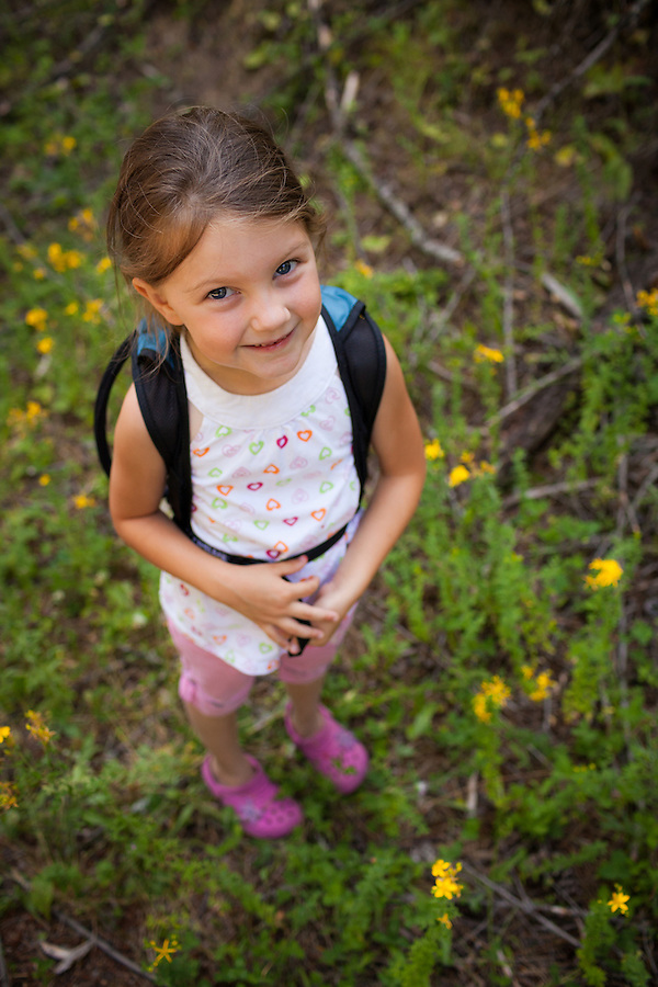 A 5 year old girl is excited to take her first hike in Northern Idaho, carrying a Camelbak hydration pack while surrounded by a field of yellow flowers.