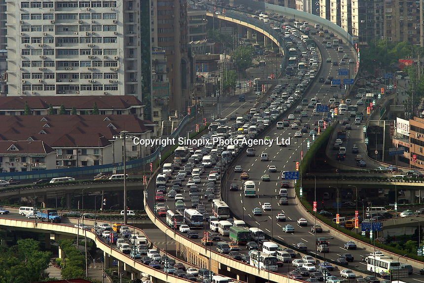 Traffic on an elevated highway in Shanghai, China. Driven by sizzling investment that has fuelled fears of inflation and bad loans, China is struggling to slow an economy that grew 9.8 percent annually for the first quarter of 2004, triggering a slew of measures taken by the coutry's central bank including the halt of all loans made to fixed-asset investment projects not approved by the government..02-JUN-04
