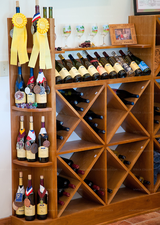 Gadino Cellars displays their wine awards at the end of decorative wine racks, behind the tasting bar.
