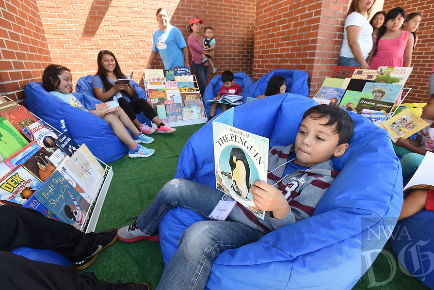 NWA Democrat-Gazette/FLIP PUTTHOFF <br /> Alexander Galves, 6, reads in a lounge area Wednesday June 21 2017 in front of The Moonshot Rocket Bus at Parson Hills Elementary in Springdale.