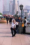 man photographing at the Bund on a sunny day in Shanghai, China, Asia