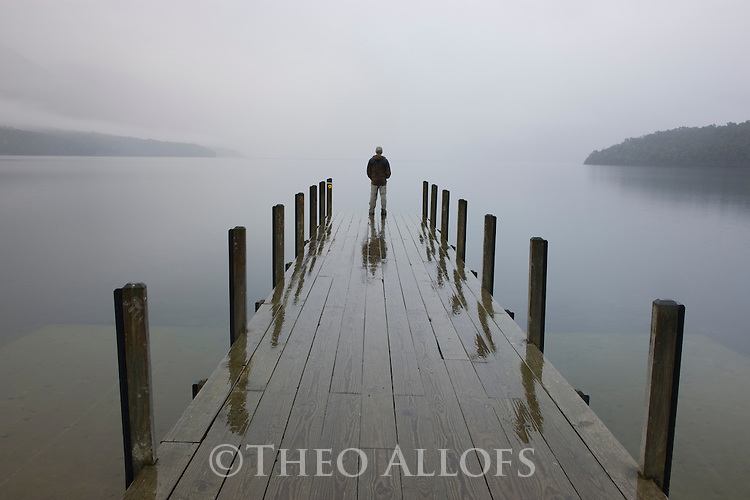 Man standing on wooden pier at Lake Rotoiti in rain; Nelson Lakes National Park, South Island, New Zealand---Model Released