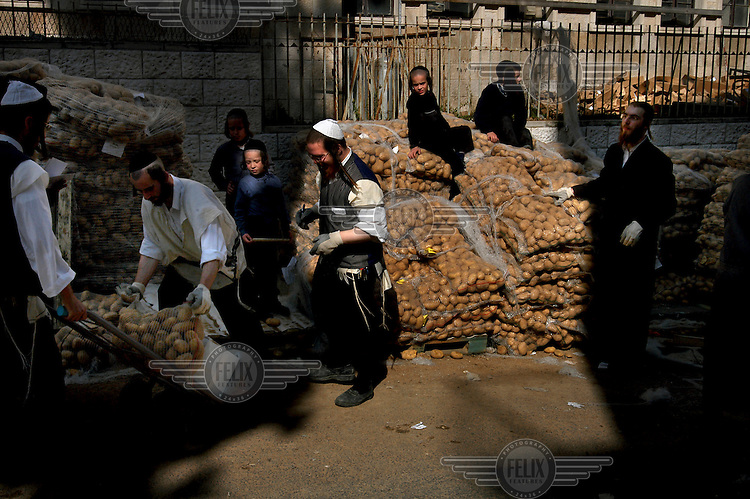 Ultra-Orthodox Jewish men load sacks of potatoes to be distributed to the needy for the upcoming Jewish holiday of Passover.