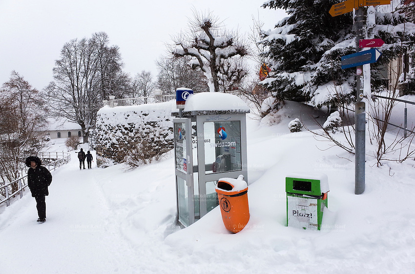 Switzerland. Canton Bern. Wengen. People walk in the snow. Swisscom public phone booth. Orange and green dustbin. Wengen is a mountain village in the Bernese Oberland of central Switzerland. Located in the canton of Bern at an elevation of 1,274 m (4,180 ft) above sea level, it is part of the Jungfrauregion and has approximately 1,300 year-round residents. 14.01.17 © 2017 Didier Ruef