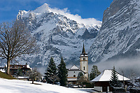 CHE, Schweiz, Kanton Bern, Berner Oberland, Wintersportort Grindelwald mit Dorfkirche an einem Wintertag vorm Wetterhorn 3.701 m | CHE, Switzerland, Bern Canton, Bernese Oberland, wintersport resort Grindelwald with church in front of Wetterhorn mountain 12.143 ft. on a sunny winter day