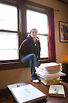 Margaret B. Jones in the living room of their Eugene, Oregon home in front of a stack of revisions of her manuscript.