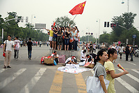 Spectators wave a flag as they stand on a street median as they watch the Nanjing, China, leg of the 2008 Olympic Torch Relay.