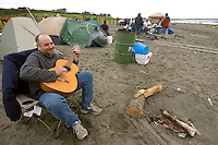 "Andy Podems, of Palmer, Alaska, strums his guitar in front of his tent in a temporary tent city that springs up on the banks of the Kenai River's mouth in Kenai, Alaska, every July during the dipnet salmon fishery. ""I'm 43 now, so I only want to spend three or four hours in the water,"" Podems joked. ""I wait until when the high tide drains and the fish move."""