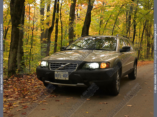 Volvo XC70 on a country road in fall nature scenery. Algonquin, Ontario, Canada.
