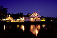 New Hampshire, Wolfeboro, NH, PJ's Dockside Restaurant reflects in the calm water at night on Lake Winnipesaukee in Wolfeboro one of the oldest summer resorts in America.