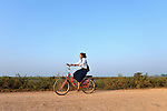 A girl rides a bike to school in the village of Chek Angkor in northern Cambodia.