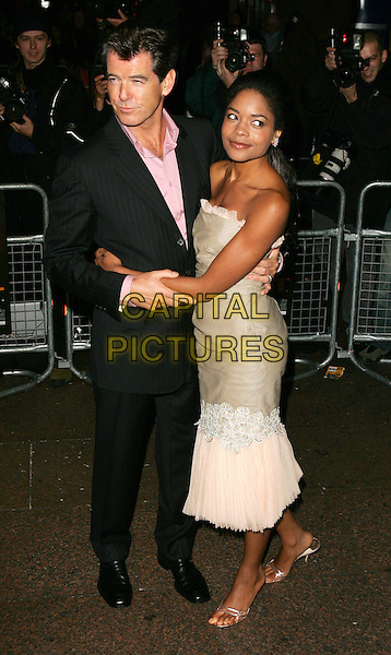 "PIERCE BROSNAN & NAOMIE HARRIS.Premiere of ""After The Sunset"", Vue Cinema, Leicester Square, London.November 2nd, 2004.full length black pinstripe suit beige strapless dress ruffles layers hug embrace gesture.www.capitalpictures.com.sales@capitalpictures.com.©Capital Pictures."