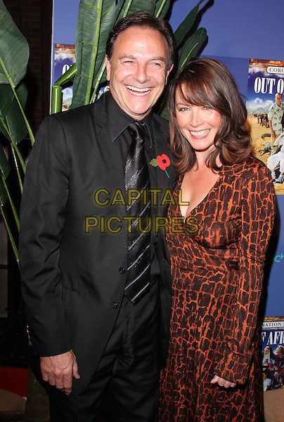 "BRIAN CAPRON & GUEST.Coronation Street ""Out Of Africa"" DVD Premiere at Odeon Cinema, The Printworks, Manchester, England..November 4th, 2008.half length black suit brown dress pattern poppy.CAP/ROS.©Steve Ross/Capital Pictures."