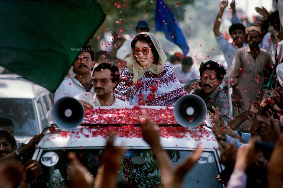 Baluchistan Province. 1986. Benazir Bhutto during her election campaign tour. People throw some roses to welcome her. ....Province du Balouchistan. 1986. Benazir Bhutto pendant sa campagne electorale. Le peuple lance des petales de roses sur son passage.