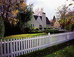 One story house with multiple windows, chimney, front yard, and white picket fence.