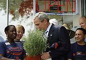 Frager's Hardware employee Yvonne Woodard (L) gives a Rosemary bush as a gift to United States President George W. Bush in front of the hardware on Capitol Hill May 5, 2006 in Washington, DC. Bush made a quick trip to the hardware store to talk about the economy and gas prices. An AP-Ipsos poll released today found 33 percent of the public approves of Bush's job performance, the lowest of his presidency. <br /> Credit: Chip Somodevilla - Pool via CNP