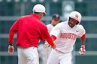 Ashford Fulmer #23 slaps hands with third base coach Mike Taylor after hitting a 2-run home run against the Texas Tech Red Raiders at Minute Maid Park on February 28, 2014 in Houston, Texas.  The Cougars defeated the Red Raiders 9-0.  (Brian Westerholt/Four Seam Images)