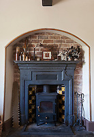 The wood-burning stove in the living room is situated in a Victorian firplace lined with the original dark blue and yellow ceramic tiles