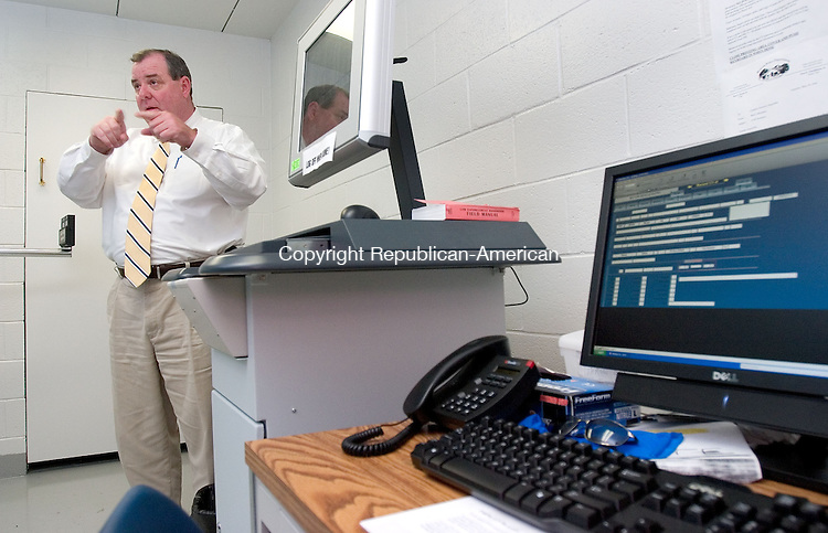 WOLCOTT, CT. 25 June 2010-062510SV11--Acting Chief Neil O'Leary explains how the department's AFIS computer is now hooked up to the department's computer system at the police station in Wolcott Friday.<br /> Steven Valenti Republican-American