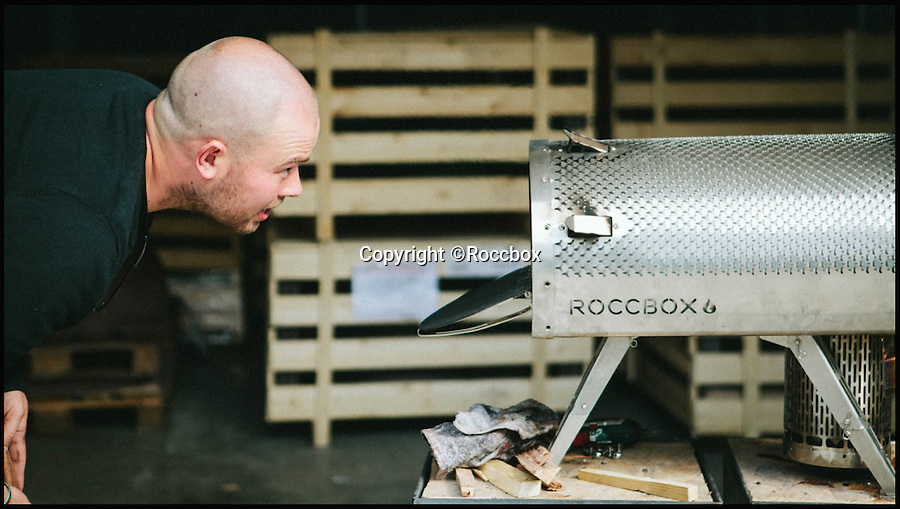 BNPS.co.uk (01202 558833)<br /> Pic: Roccbox/BNPS<br /> <br /> Tom Gozney works on an early prototype of the Roccbox.<br /> <br /> Forget barbecues in the park this summer - pizzas could soon be the in thing to cook at gatherings after a British inventor launched the world's first portable pizza oven.<br /> <br /> Just like a barbecue the lightweight device can be thrown into the boot of a car and taken to parks and campsites - but instead of grilling food it uses wood or gas to heat up its authentic stone base to blistering temperatures.<br /> <br /> Called the Roccbox, the invention is the brainchild of entrepreneur Tom Gozney, who launched his wood-fired pizza oven business six years ago after finding he couldn't cook a crispy pizza in his conventional oven.<br /> <br /> Tom, 30, from Lymington, Hants, has spent three years developing his pioneering portable pizza oven, and is now looking for backing from Virgin boss Sir Richard Branson via the billionaire's 'Pitch to Rich' scheme where the public vote for enterprising inventions.