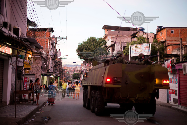 An armoured vehicle loaded with armed military drives through a street in Complexo da Mare near Rio de Janeiro's international airport. The favela consists of a complex of 16 communities, in the north zone of Rio de Janeiro. It is the largest complex of favelas, housing 130,000 residents. It is targeted for pacification as the city prepares for the 2014 World Cup and the 2016 Olympics.