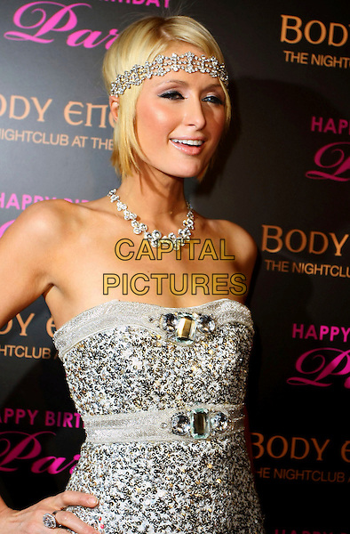 PARIS HILTON.Paris Hilton celebrates her birthday at Body English Nightclub inside the Hard Rock Resort Hotel and Casino, Las Vegas, Nevada, USA, .7th March 2009..half length silver strapless beaded shiny jewel encrusted dress embellished sparkly dress hand on hip headband head band  sequined .CAP/ADM/MJT.©MJT/Admedia/Capital Pictures