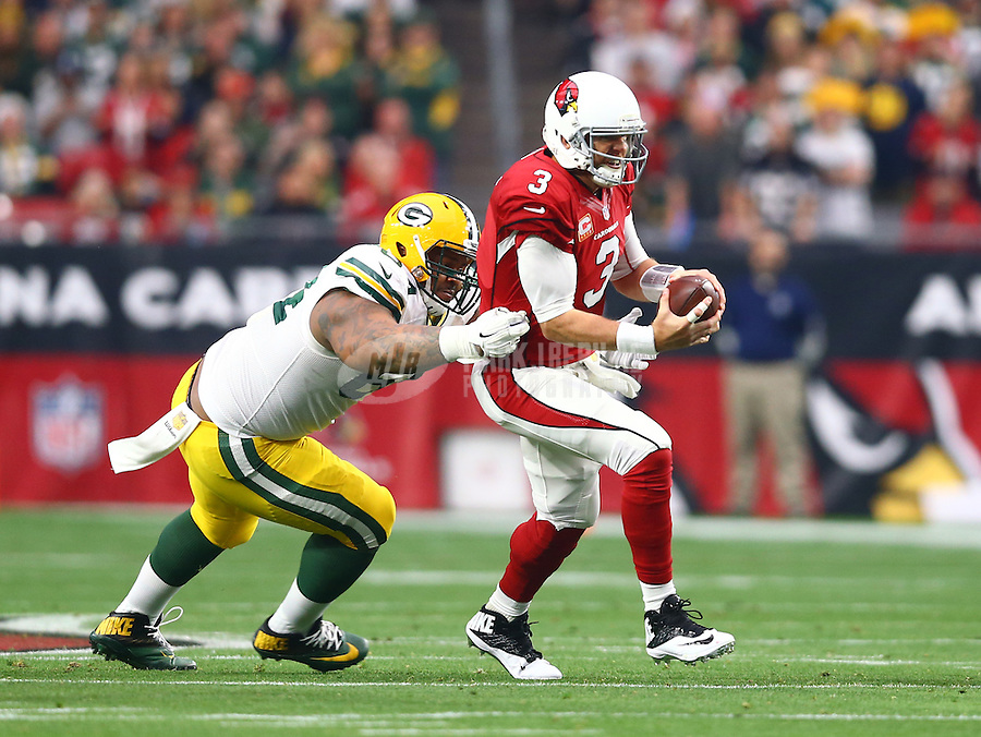 Dec 27, 2015; Glendale, AZ, USA; Arizona Cardinals quarterback Carson Palmer (3) is tackled by Green Bay Packers defensive tackle Mike Pennel (64) at University of Phoenix Stadium. Mandatory Credit: Mark J. Rebilas-USA TODAY Sports