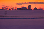 dramatic sunset with barn and farmhouse silhouetted