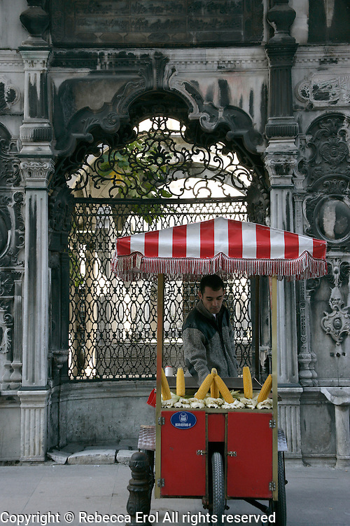 Selling corn on the cob next to an Ottoman tomb in Eminonu, Istanbul, Turkey