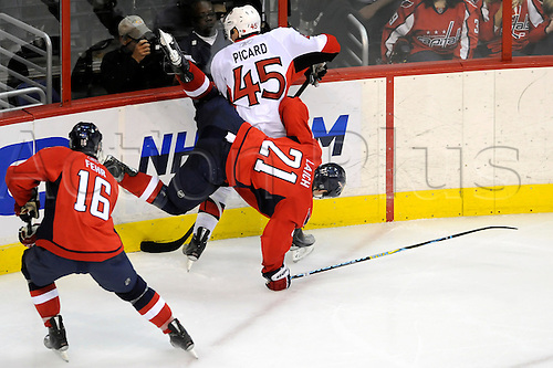 07 January 2010:  Washington Capitals center Brooks Laich (21) is dumped to the ice by Ottawa Senators defenseman Alexandre Picard (45) in action at the Verizon Center in Washington, D.C.  The Washington Capitals defeated the Ottawa Senators 5-2. Photo by Mark Goldman/Actionplus, UK Licenses Only.