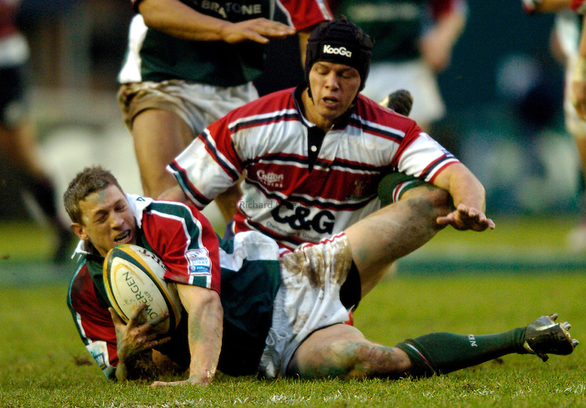 Photo: Richard Lane..Leicester Tiger v Gloucester. Powergen Cup. 18/12/2004..Scott Bemand collects the ball as Henry Paul challenges.