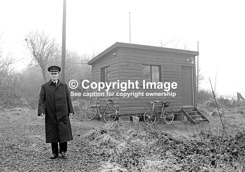 Policeman on guard duty at Ahoghill, Co Antrim, at the home of the N Ireland Ulster Unionist Prime Minister Captain Terence O'Neill. A second policeman is inside the wooden hut where there are telephone and two-way radio links. Note the means of transport - just two bicycles. With the benefit of hindsight a wooden hut would have provided little in the way of protection against a gun or bomb attack. January 1965. 196501000003<br />