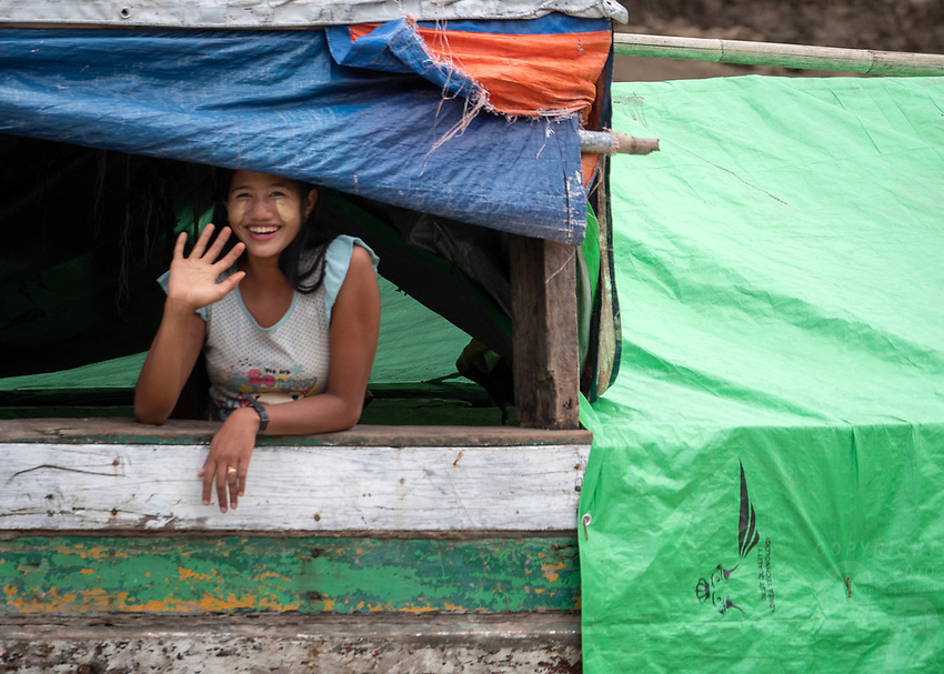 Girl waving from a boat on the Lay Mro River, Rakhine State, Myanmar
