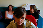 Laetizia in front of her computer and behind her Virginie a volunteer and Patrizia her mother...Partinico, Sicily, Italy - June 2006.