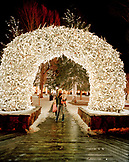 USA, Wyoming, Jackson Hole, Mother and children standing under an arch made of antlers in downtown Jackson Hole